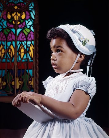1960s RELIGIOUS LITTLE AFRICAN AMERICAN GIRL WEARING WHITE HAT AND DRESS HOLDING BIBLE STANDING BY STAINED GLASS WINDOW IN CHURCH Stock Photo - Rights-Managed, Code: 846-03165101