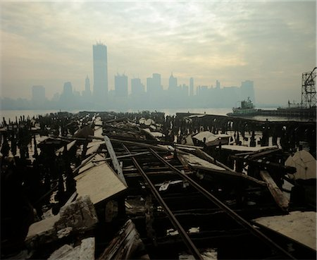 1970s SKYLINE OF DOWNTOWN MANHATTAN FROM ROTTING BROOKLYN PIER SHADOW OF WORLD TRADE CENTER UNDER CONSTRUCTION Stock Photo - Rights-Managed, Code: 846-03165569
