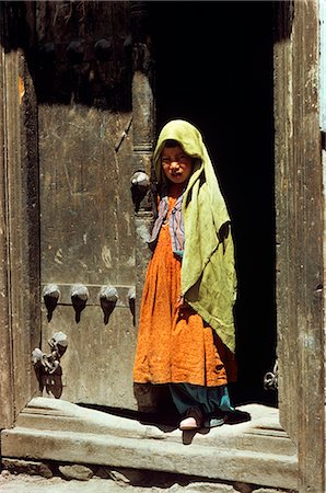 LITTLE GIRL STANDING IN THE DOORWAY TYPICAL NEPALESE BRASS-STUDDED DOOR NEPAL Stock Photo - Rights-Managed, Code: 846-03165705