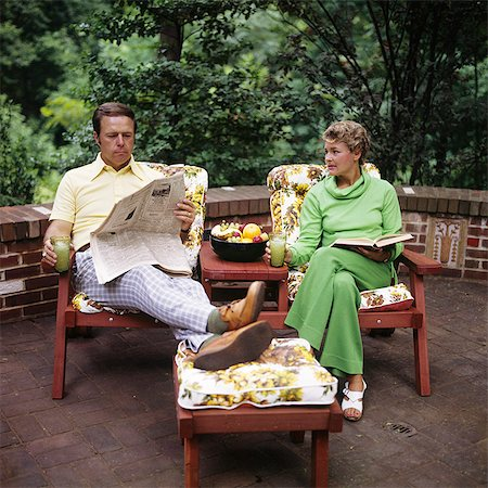 1970s COUPLE MAN WOMAN MIDDLE AGED SITTING PATIO DECK READING BOOK NEWSPAPER Stock Photo - Rights-Managed, Code: 846-03165833