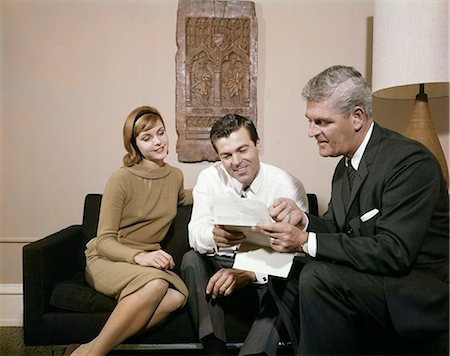 1960s COUPLE MAN WOMAN LIVING ROOM TALKING TO SALESMAN LOOKING CONTRACT INSURANCE Stock Photo - Rights-Managed, Code: 846-03165859