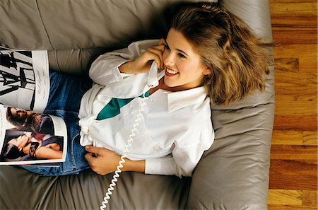 1990s YOUNG WOMAN IN WHITE BLOUSE RECLINING ON LEATHER SOFA WHILE TALKING ON PHONE Stock Photo - Rights-Managed, Code: 846-03165919