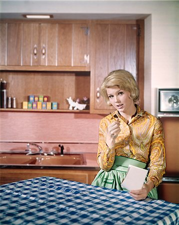 1960s SERIOUS BLONDE HOUSEWIFE MAKING SHOPPING LIST AT KITCHEN TABLE Stock Photo - Rights-Managed, Code: 846-03166019