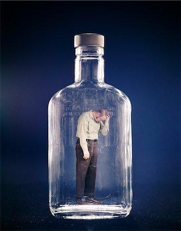 1970s SAD DEPRESSED MAN TRAPPED INSIDE GLASS BOTTLE ALCOHOLISM ALCOHOLIC ADDICTED ADDICTION Stock Photo - Rights-Managed, Code: 846-03166064