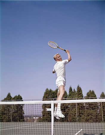 1970s MAN PLAYING TENNIS JUMPING IN MID AIR SWINGING RACKET TO HIT BALL ACTION RECREATION EXERCISE Stock Photo - Rights-Managed, Code: 846-03166124