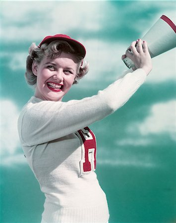 1940s 1950s SMILING TEEN GIRL CHEERLEADER WEARING VARSITY LETTER SWEATER HOLDING MEGAPHONE Stock Photo - Rights-Managed, Code: 846-03166371