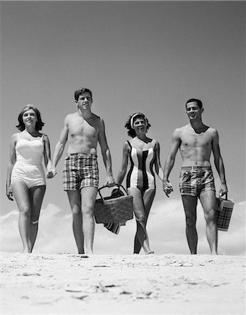 1960s TEENAGE COUPLES WEARING BATHING SUITS ON BEACH CARRYING PICNIC BASKETS Stock Photo - Rights-Managed, Code: 846-03163206