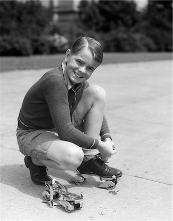 roller skate - 1930s SMILING BOY FASTENING ON STREAMLINE METAL ROLLER SKATES Stock Photo - Rights-Managed, Code: 846-03163203