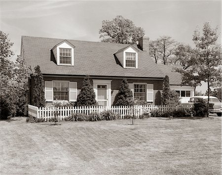 1950s 1960s SUBURBAN BRICK HOUSE PICKET FENCE DORMER WINDOWS CAR IN DRIVEWAY Stock Photo - Rights-Managed, Code: 846-03163230