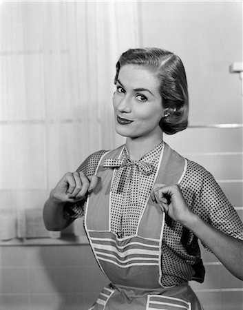1950s HOUSEWIFE WEARING APRON WITH THUMBS PROUDLY HOOKED ON STRAPS Stock Photo - Rights-Managed, Code: 846-03163304