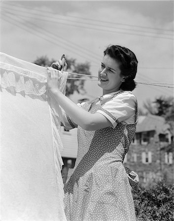 photo of 1940s housewife - 1940s WOMAN HANGING LAUNDRY ON CLOTHESLINE OUTDOORS Stock Photo - Rights-Managed, Code: 846-03163336