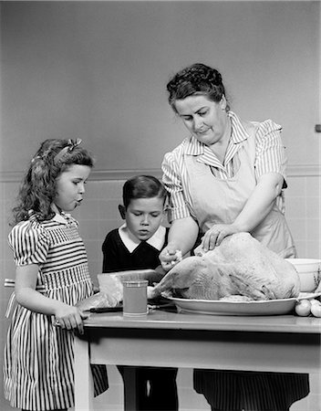 photos of 1940s women in kitchen - 1940s MOTHER SON DAUGHTER KITCHEN TURKEY DINNER Stock Photo - Rights-Managed, Code: 846-03163352