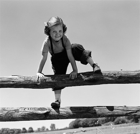 1940s 1950s SMILING GIRL CLIMBING OVER WOODEN FENCE Stock Photo - Rights-Managed, Code: 846-03163439