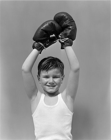 1940s CHILD WEARING BOXING GLOVES HOLDING HANDS ABOUT HEAD Stock Photo - Rights-Managed, Code: 846-03163441