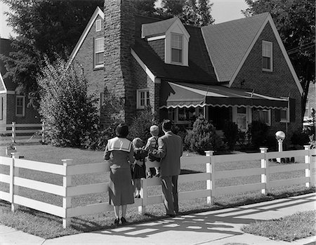 1950s FAMILY STANDING BY WHITE FENCE LOOKING AT BRICK HOUSE Stock Photo - Rights-Managed, Code: 846-03163498