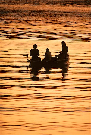 TWO MEN AND CHILD IN CANOE FISHING IN FRESHWATER AT SUNSET Stock Photo - Rights-Managed, Code: 846-03163673