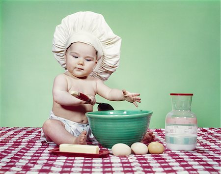 1960s BABY WEARING CHEF HAT SPOON MIXING BOW AND BAKING INGREDIENTS Stock Photo - Rights-Managed, Code: 846-03163753