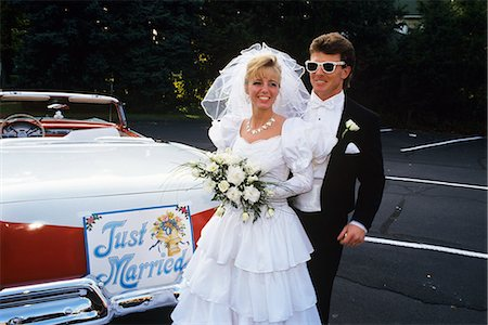 1991 BRIDE AND GROOM STANDING NEXT TO VINTAGE CONVERTIBLE FORD CAR Stock Photo - Rights-Managed, Code: 846-03163773