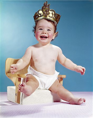 1960s SMILING HAPPY BABY WEARING CROWN SITTING ON BOOSTER SEAT CHAIR Stock Photo - Rights-Managed, Code: 846-03163925
