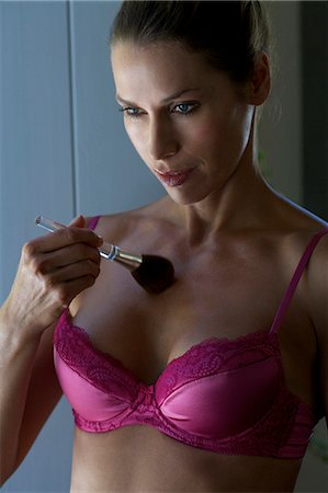 Mature woman in pink bra applying bronzer with a brush Stock Photo - Rights-Managed, Code: 847-05606942