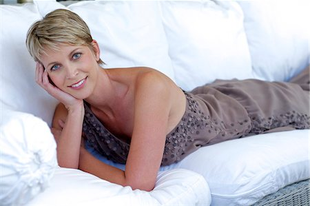 Elegant, mature woman lying on white settee Stock Photo - Rights-Managed, Code: 847-05606985