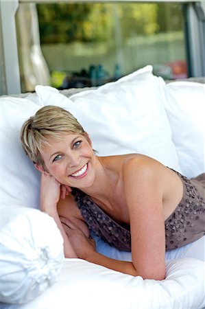 Elegant, mature woman lying on white settee Stock Photo - Rights-Managed, Code: 847-05606987