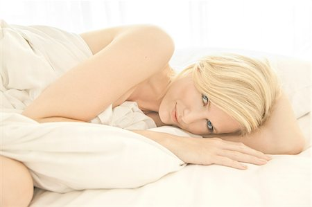 Blonde woman lying on a bed wrapped in a sheet Stock Photo - Rights-Managed, Code: 847-05607036