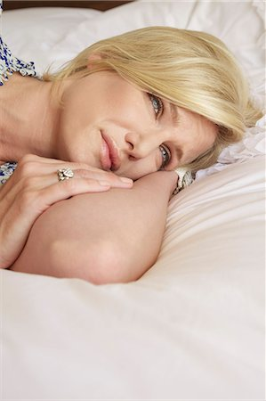 sad girls - Blonde woman with a sad expression lying on a bed Stock Photo - Rights-Managed, Code: 847-05607032