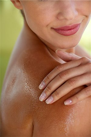 Beautiful girl rubbing massage oil into her skin Stock Photo - Rights-Managed, Code: 847-05809884