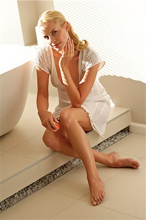 Beautiful blonde woman applying lotion to her legs Stock Photo - Rights-Managed, Code: 847-05818405