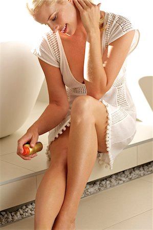 Beautiful blonde woman applying lotion to her legs Stock Photo - Rights-Managed, Code: 847-05818412