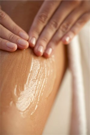 Close up of rubbing lotion into thigh with two hands, robe visable on the right. Stock Photo - Rights-Managed, Code: 847-02780018