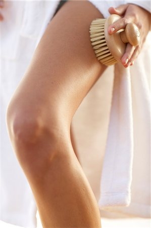 Close up of body brushing thigh in a white robe with a small wooden brush Stock Photo - Rights-Managed, Code: 847-02780010