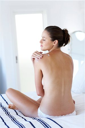 Beautiful naked woman sitting up moisturising Stock Photo - Rights-Managed, Code: 847-02782724