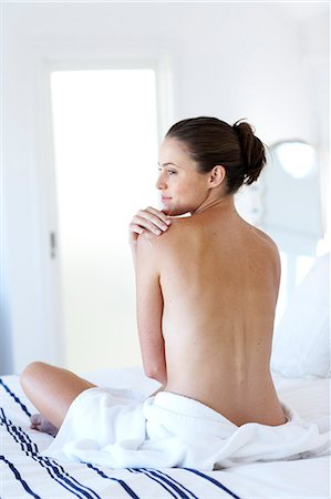 Beautiful naked woman sitting up moisturising Stock Photo - Rights-Managed, Code: 847-02782725