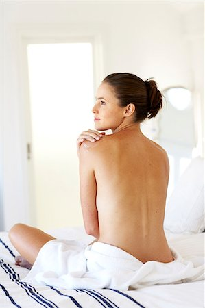 Beautiful naked woman sitting up moisturising Stock Photo - Rights-Managed, Code: 847-02782726