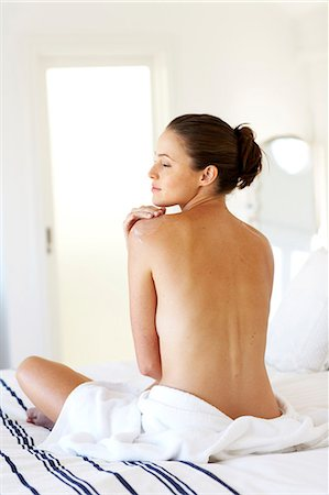 Beautiful naked woman sitting up moisturising Stock Photo - Rights-Managed, Code: 847-02782727