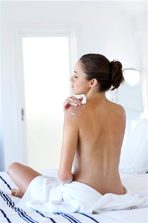 Beautiful naked woman sitting up moisturising Stock Photo - Rights-Managed, Code: 847-02782728