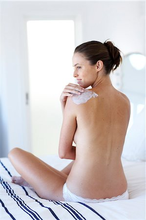 Beautiful naked woman sitting up moisturising Stock Photo - Rights-Managed, Code: 847-02782722