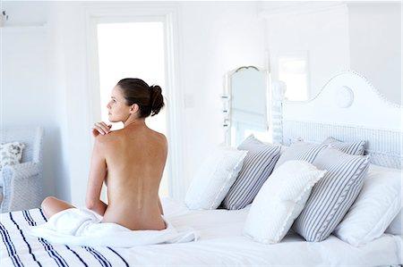 Beautiful naked woman sitting up moisturising Stock Photo - Rights-Managed, Code: 847-02782735