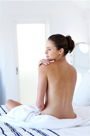 Beautiful naked woman sitting up moisturising Stock Photo - Rights-Managed, Code: 847-02782730