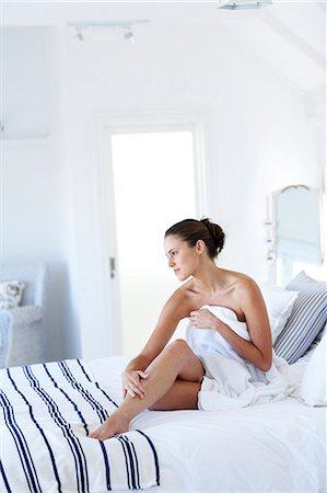 Beautiful naked woman sitting up moisturising legs Stock Photo - Rights-Managed, Code: 847-02782749