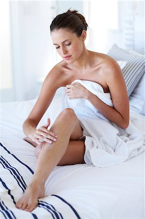 Cropped photo of beautiful naked woman sitting up moisturising legs Stock Photo - Rights-Managed, Code: 847-02782740