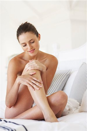 Cropped beautiful naked woman sitting up moisturising legs Stock Photo - Rights-Managed, Code: 847-02782770
