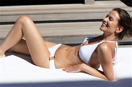 Landscape of a beautiful lady lying down in villa wearing bikini Stock Photo - Rights-Managed, Code: 847-03758016
