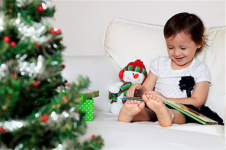 Young girl reading a book, Christmas tree in foreground Stock Photo - Rights-Managed, Code: 849-06466248