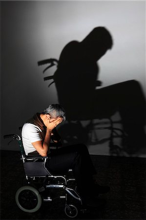 people in panic - Man sitting in a wheelchair with head in hands with dramatic shadow on the wall Stock Photo - Rights-Managed, Code: 849-06466269