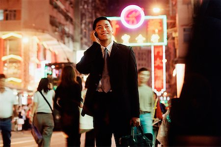 Hong Kong, male executive using cellular phone, carrying briefcase Stock Photo - Rights-Managed, Code: 849-02865267