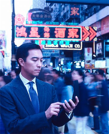 Male executive dialing cellular phone in busy street, neon lights in background. Stock Photo - Rights-Managed, Code: 849-02865886