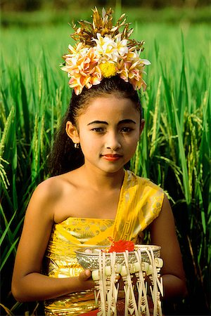 Indonesia, Bali, Young Balinese dancer in costume with offerings in rice paddy. Stock Photo - Rights-Managed, Code: 849-02866239